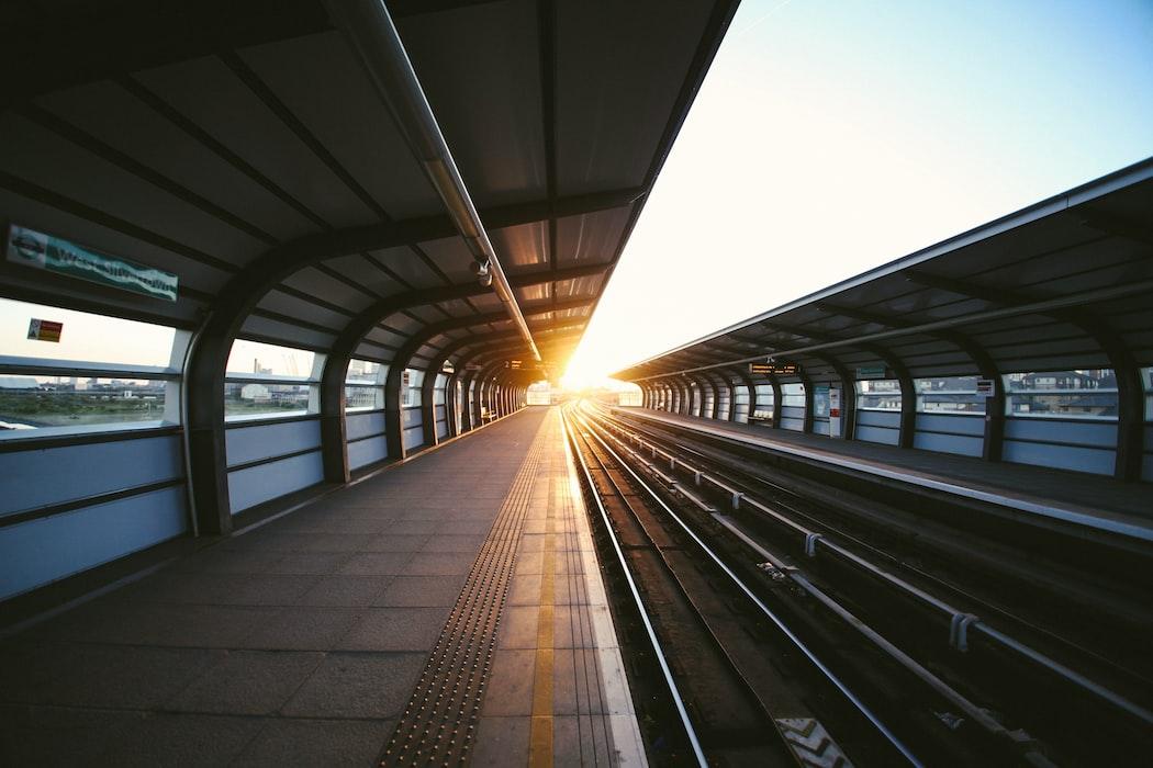 Imagen gratis del andén de una parada de metro exterior con el sol de fondo